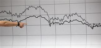 Работник Мадридской фондовой биржи указывает на график с фондовыми котировками, 17 мая 2012 года. Плачевное состояние европейской экономики сказывается на отношении глобальных инвесторов к активам развивающихся рынков, и в этих условиях фонды, ориентированные на акции РФ, уже два месяца не получают чистого притока средств. REUTERS/Paul Hanna