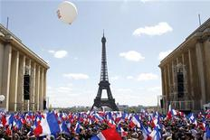 Supporters wave flags as they wait for France's President and UMP party candidate for his re-election in the 2012 French presidential elections, Nicolas Sarkozy, to deliver his speech at Trocadero square during a campaign rally in front the Eiffel Tower in Paris May 1, 2012. REUTERS/Gonzalo Fuentes