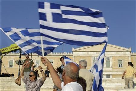 A man holds a Greek flag before a conservative New Democracy party rally at Syntagma square in Athens June 15, 2012. Greece holds general parliamentary elections on June 17. REUTERS/Pascal Rossignol