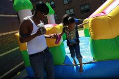 Joseph Perry helps his daughter Kira Perry during a Father's Day carnival at the Van Dyke Community Center in Brownsville, New York June 16, 2012. REUTERS/Eric Thayer