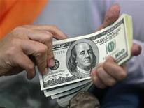 Женщина держит пачку купюр по $100 в Джакарте, 13 июня 2012 года. Российский агрохимический холдинг Фосагро сообщил, что в первом квартале 2012 года увеличил чистую прибыль по МСФО на 29 процентов до $266 миллионов на фоне роста продаж удобрений. REUTERS/Beawiharta