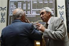 Traders talk in front of computer boards at the stock exchange in Madrid June 15, 2012. REUTERS/Andrea Comas