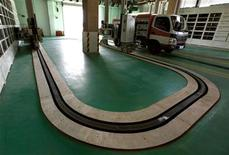 An electric vehicle waits for a battery exchange robot at China's largest electric vehicle battery recharging station located in Beijing May 30, 2012. REUTERS/David Gray