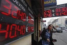 Женщина проходит мимо вывесок обменного пункта в Москве 8 июня 2012 года. Рубль умеренно подешевел в начале торгов вторника, следуя утренней динамике нефтяного и фондовых рынков; дальнейшее поведение российской валюты будет зависеть как от внешних факторов, так и от внутренних денежных потоков и активности экспортеров в налоговый период. REUTERS/Maxim Shemetov