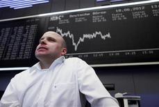 Трейдер стоит перед информационным табло на бирже во Франкфурте-на-Майне, 18 июня 2012 года. Европейские рынки акций открылись ростом. REUTERS/Alex Domanski