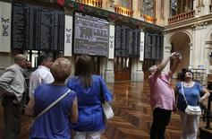 Visitors stand near electronic boards at the stock exchange in Madrid June 15, 2012. REUTERS/Andrea Comas