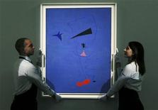Gallery assistants pose with Joan Miro's Peinture (Etoile Blue) which is on display at Sotheby's in central London, June 14, 2012. REUTERS/Olivia Harris