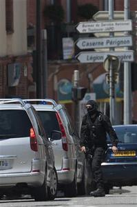 A special French GIPN intervention police member arrives at the scene where a man claiming to be a member of al Qaeda has taken four hostages, including the bank manager, in a bank in Toulouse, June 20, 2012. The man took several hostages in a branch of French bank CIC and fired a shot after an attempted armed robbery apparently went wrong, a police union official reported. REUTERS-Bruno Martin