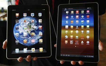 An employee of South Korean mobile carrier KT holds a Samsung Electronics' Galaxy Tab 10.1 tablet (R) and Apple Inc's iPad tablet as he poses for photos at a registration desk at KT's headquarters in Seoul August 10, 2011. REUTERS/Jo Yong-Hak