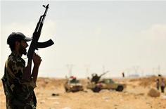 Ливийский повстанец у НПЗ в городе Рас-Лануф 27 августа 2011 года. Российская нефтяная компания Татнефть надеется вернуться в Ливию, как только ситуация там успокоится, сказал глава компании, в мае сообщившей акционерам, что она не уверена в перспективах продолжения работы в пережившей революцию африканской стране. REUTERS/Esam Al-Fetori