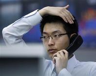 Трейдер Korea Exchange Bank говорит по телефону в офисе в Сеуле, 4 ноября 2011 года. Азиатские фондовые рынки, кроме Японии, снизились, разочарованные действиями ФРС США и спадом производственной активности Китая. REUTERS/Jo Yong-Hak