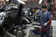 An employee works on a car engine along a Geely Automobile Corporation assembly line in Cixi, Zhejiang province June 21, 2012. REUTERS/Carlos Barria