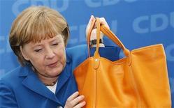 Канцлер Германии Ангела Меркель достает сумку перед началом съезда ее партии христианских демократов в Берлине 11 июня 2012 года. Лидеры Германии, Франции, Италии и Испании попытаются найти способы восстановления доверия в еврозоне на заседании в Риме в пятницу в преддверии полноценного саммита Евросоюза на следующей неделе. REUTERS/Fabrizio Bensch