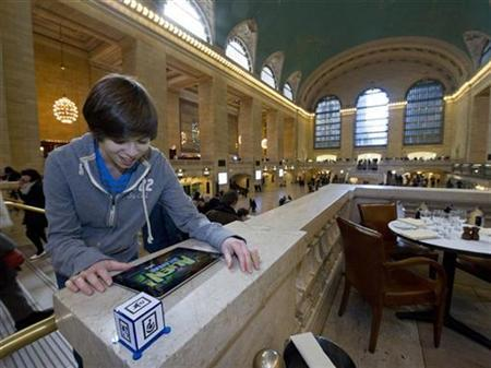 Josh Rubinstein, 15, utilizes augmented reality technology with AppGear's ''Alien Jailbreak'' on his iPad as he plays the new generation of toy at Grand Central Station during the American International Toy Fair in New York, February 13, 2012. REUTERS/Ray Stubblebine/WowWee/Insider Images/Handout