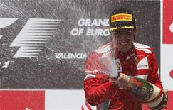 Piloto da Fórmula 1 Fernando Alonso, da Espanha, espirra champagne durante cerimônia do pódio após vencer o Grande Prêmio da Europa de F1 no circuito de rua de Valência. 24/06/2012 REUTERS/Albert Gea