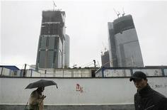 Люди проходят мимо стройки в Москве, 17 октября 2008 года. Рабочая неделя в Москве будет пасмурной, ожидают синоптики. REUTERS/Denis Sinyakov