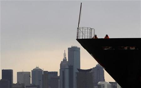 A container ship travels pasts the skyline of Melbourne August 31, 2010. REUTERS/Mick Tsikas