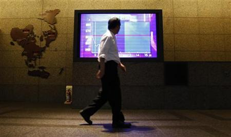 A man passes a television screen displaying a graph of Japan's Nikkei share average at a lobby of a brokerage in Tokyo June 12, 2012. REUTERS/Yuriko Nakao/Files