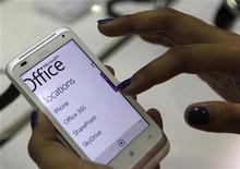 Посетительница выставки в Тайбэй пользуется ОС Windows Phone на смартфоне HTC Radar, 5 июня 2012 года. Microsoft Corp договорилась о покупке за $1,2 миллиарда наличными соцсетевого ресурса Yammer Inc, который позволит ей предоставлять услуги, аналогичные сервисам Facebook Inc, корпоративным клиентам. REUTERS/Pichi Chuang