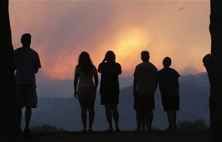 People watch a giant smoke plume rising from the Waldo Canyon Fire during sunset, west of Colorado Springs June 24, 2012. REUTERS/Rick Wilking