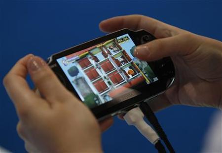 A visitor plays with the new Playstation PS Vita at the Sony Playstation exhibition stand during the Gamescom 2011 fair in Cologne August 17, 2011. REUTERS/Ina Fassbender/Files
