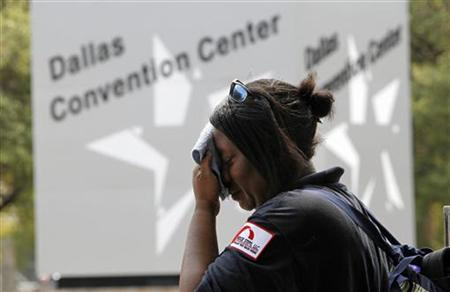 Tamika Davis wipes her face while waiting for a bus in Dallas, Texas, August 1, 2011. REUTERS/Tim Sharp
