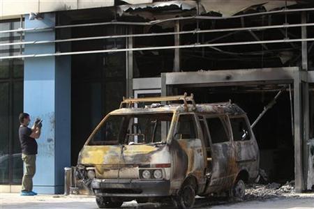 A police investigator gathers evidence following an attack on Microsoft's Greek headquarters at Marousi suburb, north of Athens June 27, 2012. REUTERS/John Kolesidis