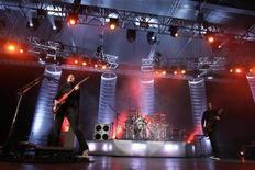 """Matthew Bellamy (L), Dominic Howard (C) and Chris Wolstenholme, of the British rock band Muse, perform during a concert in Hong Kong March 3, 2007. REUTERS/Paul Yeung (CHINA) Matthew Bellamy (esquerda), Dominic Howard (centro) e Chris Wolstenholme, da banda britânica de rock Muse, apresentam-se em um show em Hong Kong, no Japão. """"Survival"""", da Muse, será a canção oficial dos Jogos Olímpicos de Londres 2012, anunciaram os roqueiros na quarta-feira. 3/03/2007 REUTERS/Paul Yeung"""