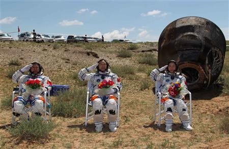 Chinese astronauts Jing Haipeng (C), Liu Wang (L) and Liu Yang, China's first female astronaut, salute in front of the re-entry capsule of China's Shenzhou 9 spacecraft in Siziwang Banner, Inner Mongolia Autonomous Region June 29, 2012. REUTERS/Xinhua/Ren Junchuan