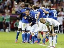 Игроки итальянской сборной празднуют победу над Германией в полуфинальном матче чемпионата Европы в Варшаве 28 июня 2012 года. Сборная Италии одолела в четверг одного из главных фаворитов чемпионата Европы, Германию, благодаря двум великолепным голам Марио Балотелли и вышла в финал турнира, где сыграет с действующими обладателями титула - испанцами. REUTERS/Thomas Bohlen