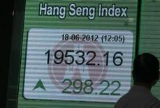 Мужчина смотрит на экран со значением и динамикой индекса Hang Seng в Гонконге 18 июня 2012 года. Азиатские фондовые рынки выросли благодаря договоренностям лидеров Европы на саммите в четверг. REUTERS/Tyrone Siu