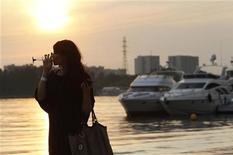 Посетительница московской выставки Summer Fair пьет из бокала 2 июля 2010 года. Уикенд в Москве будет теплым и солнечным, ожидают синоптики. REUTERS/Sergei Karpukhin
