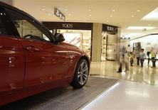 Visitors walk past a BMW 328i sports car display at Plaza Indonesia in Jakarta June 25, 2012. Luxury motors are a sign of the growing wealth of Indonesia's middle class, the bulging wallets of its rich after years of a mining and stock market boom, and the desire of both to convert their cash into the most prestigious set of wheels they can afford. Picture taken June 25, 2012. REUTERS/Beawiharta