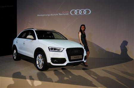 A model stands near a new Audi Q3 during its launch in Jakarta June 28, 2012. REUTERS/Supri