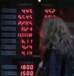 Женщина смотрит курс валют около операционной кассы в Буэнос-Айресе, 28 мая 2012 года. Евро снижается к доллару по мере прохождения эйфории, вызванной состоявшимся на прошлой неделе саммитом Евросоюза. REUTERS/Marcos Brindicci