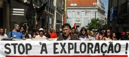 A demonstrator holds a banner that reads, ''Stop the exploitation,'' during a protest against unemployment in Lisbon June 30, 2012. REUTERS/Hugo Correia