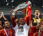 Jogadores de espanhóis, Juan Mata, Fernando Torres e Andres Iniesta (E-D) levantam o troféu, após derrotarem a Itália e ganharem a final da Eurocopa 2012 no Estádio Olimpico em Kiev. 02/07/2012 REUTERS/Eddie Keogh