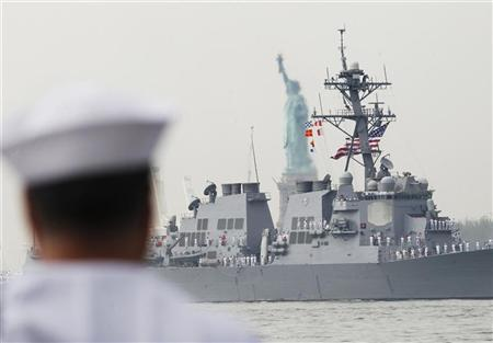 A member of the U.S. Navy watches the USS Roosevelt as it passes the Statue of Liberty in New York Harbor, while arriving for the 25th annual Fleet Week celebration in New York, May 23, 2012. REUTERS/Brendan McDermid