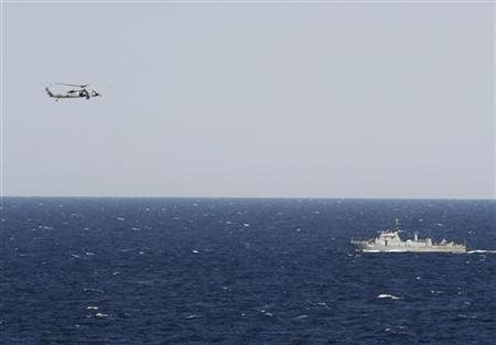 A helicopter from the Nimitz-class aircraft carrier USS Abraham Lincoln (CVN 72) hovers over an Iranian patrol ship during a transit through the Strait of Hormuz, February 14, 2012. REUTERS/Jumana El Heloueh/Files