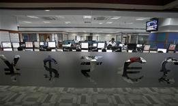 Символы мировых валют в помещении трейдинговой компании в Бомбее, 24 мая 2012 года. Евро и доллар снизились во вторник, так как слабые макроэкономические данные в Европе и США укрепили мнение о возможных дальнейших действиях центробанков в обоих регионах. REUTERS/Vivek Prakash
