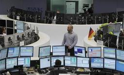 Traders work at their desks at the Frankfurt stock exchange July 2, 2012. REUTERS/Alex Domanski