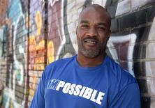 """Filmmaker DeWayne Wilkerson wears his 'I'm Possible' t-shirt as he leans against a graffiti painted building near downtown Detroit, Michigan June 27, 2012. Convicted crack dealer Wilkerson would be in prison until 2015 if not for changes in Michigan's controversial """"mandatory minimum"""" laws. Instead he has made a film. """"The Greatest Gift 2.0,"""" which Wilkerson began working on after his 2009 release, premiered last weekend at one of Detroit's largest churches and is booked for several other screenings in coming weeks. REUTERS/Rebecca Cook"""