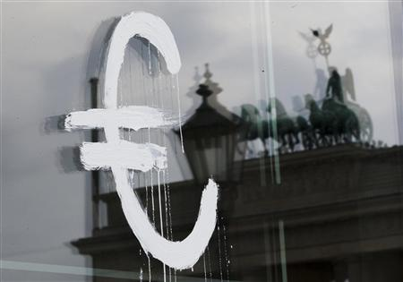 The sign of the Euro currency is painted onto the glass door of the Academy of Arts in Berlin as the Brandenburg Gate is reflected on it July 3, 2012. REUTERS/Thomas Peter
