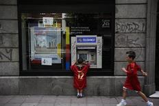 Мальчик в форме сборной Испании по футболу снимает деньги с банкомата в Мадриде, 1 июля 2012 года. Испании придется очень сильно постараться, чтобы избежать необходимости обращаться за полноценной международной финансовой помощью, несмотря на шаги, принятые на саммите Евросоюза, призванные помочь банкам-должникам и снизить стоимость заимствования для страны. REUTERS/Susana Vera