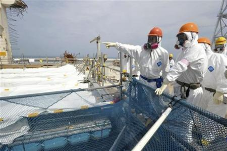 Goshi Hosono (wearing pink armband), Japan's environment minister and minister in charge of the response to the nuclear crisis, inspects a pool containing spent fuel rods at the No. 4 reactor building at Tokyo Electric Power Co's (TEPCO) tsunami-crippled Fukushima Daiichi nuclear power plant in Fukushima prefecture May 26, 2012. REUTERS/Toshiaki Shimizu/Pool/Files