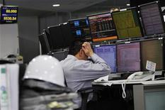Трейдер работает в торговом зале биржи в Токио, 25 марта 2011 года. Азиатские фондовые рынки закрылись разнонаправлено в ожидании решений Европейского Центробанка и Банка Англии о процентных ставках. REUTERS/Toru Hanai
