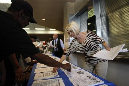 Carlene Gepner of WorkSource hands out job applications at the 11th annual Skid Row Career Fair the Los Angeles Mission in Los Angeles, California, May 31, 2012. REUTERS/David McNew