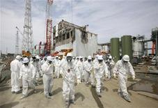 Members of the media and Tokyo Electric Power Co. (TEPCO) employees, wearing protective suits and masks, walk in front of the No. 4 reactor building at the tsunami-crippled Fukushima Daiichi nuclear power plant in Fukushima prefecture May 26, 2012. REUTERS/Tomohiro Ohsumi/Pool