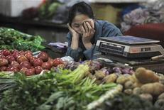 Продавщица овощей на рынке в Хэфэй уснула в ожидании покупателей, 11 мая 2012 года. Китаю будет сложно достичь 10-процентного ориентира роста торговли в этом году, считает вице-премьер Ван Цишань, подчеркивая трудности, с которыми столкнулась вторая мировая экономика. REUTERS/Stringer