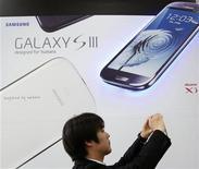 Мужчина делает снимок перед рекламным плакатом Samsung Galaxy S III в магазине в Токио, 28 июня 2012 года. Головокружительные продажи смартфонов Galaxy подтолкнут операционную прибыль Samsung Electronics во втором квартале до рекордных $5,9 миллиарда. REUTERS/Yuriko Nakao